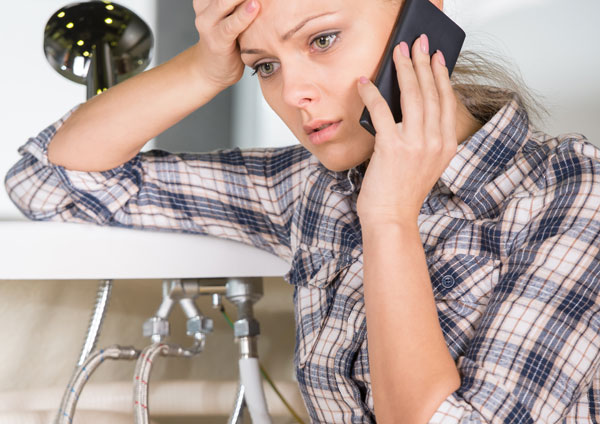 Distressed woman making phone call over water pipes