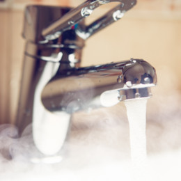Mixer tap pouring steamy hot water